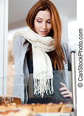Woman in scarf looking at the bakery window