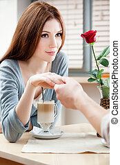 Woman at the cafe hand in hand with her boyfriend
