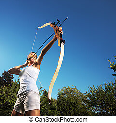 Female archer - Attractive woman bending a bow and aiming in...