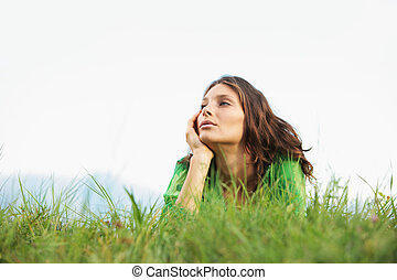 Beauty in nature - Young woman lying on the grass looking at...