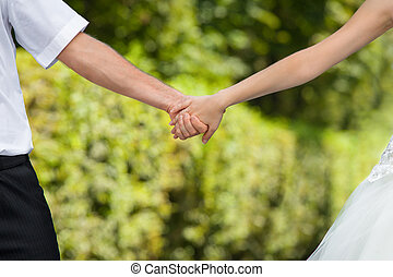 wedding hands - Bride and groom holding hands with wedding...