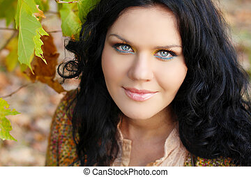 Closeup of brunette woman with blue eyes, outdoors portrait....