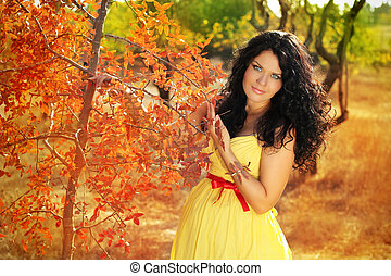 Beautiful pregnant woman relaxing outside in the park, autumn