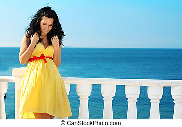 Young beautiful pregnant woman in dress over blue sky, ocean