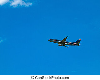 A Commercial Airliner Taking Off into a Partly Cloudy Blue...