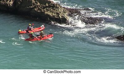Red  canoes  near rocks in the sea