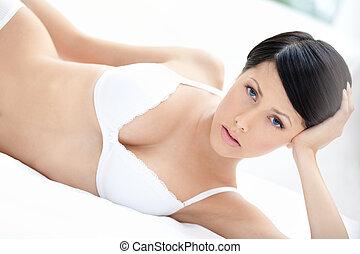 Woman in underwear is lying in the bedstead - Woman in...