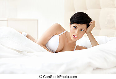 Woman in white bra is lying in the bedstead