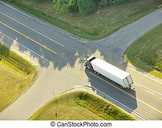 TRUCK AT CROSSROADS - Aerial view of a truck approaching a...