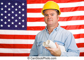 Building America - Construction worker with blueprints in...