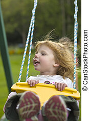 Girl on Swing - A young girl on a playground swing.