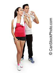man and woman drinking water after fitness - Smiling young...