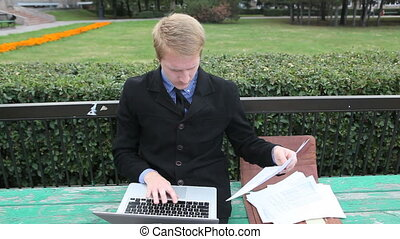 Work outdoor - Confident businessman holding document and...