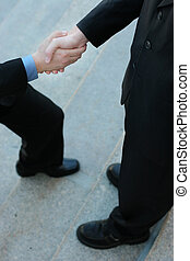 Businessman Stepping Up - Businessman Gives a Handshake...