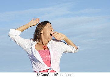 Tired woman yawning sky background