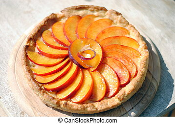 fruit cake covered with fresh slices of peaches