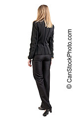 back view of walking business woman. going young girl in...