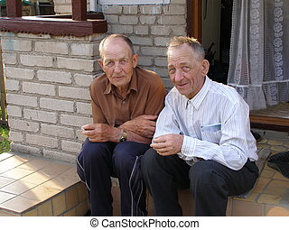 Two old men - two brother, old men, sit on the stairs of...