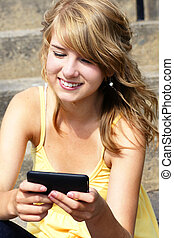 Teenager texting on mobile or cell phone - Young woman,...