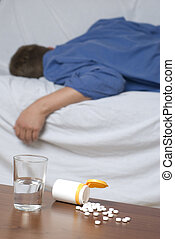 Sleeping pills - Glass of water and sleeping pills on the...