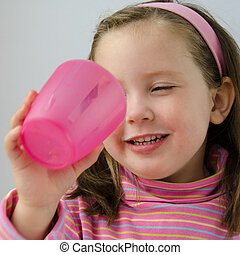 Little girl finishes glass of milk - Pretty little girl with...