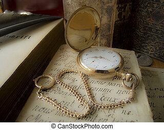ancient golden pocketwatch lying on an antique handwritten...