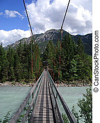 a swing bridge leading pedestrians across the Lech in Tirol,...