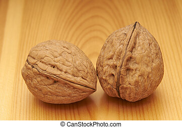 Two walnuts on a wood canvas