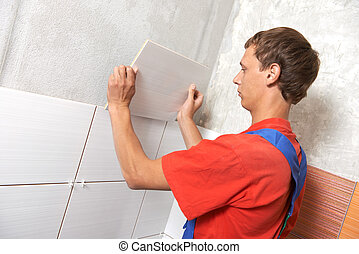 tiler at home renovation work - tiler installing wall tile...