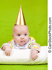 happy childhood - The kid in a celebratory cap lies on a...