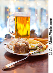 The big mug of beer and cold dishes on a little table at...