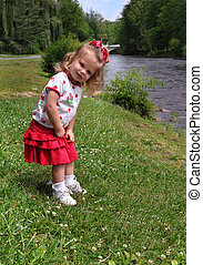 Adorable Explorer - Little girl explores the banks of the...