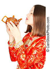 Asian woman drinking Chinese tea from the teapot in Kimono...