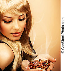 Girl hold coffee beans - Closeup portrait of pretty blonde...