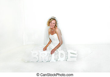 Bride to be - Bride holds letters spelling BRIDE as she sits...