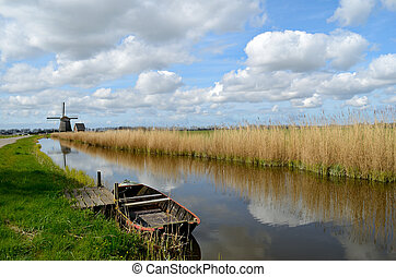 Old boat in a ditch in Holland - Typical landscape in...