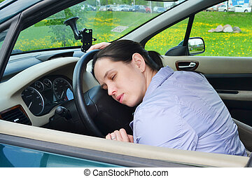 Young girl sleeps in her car.