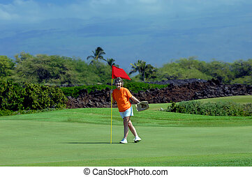 Big Smile During Golf Game - Woman stands besides hole...