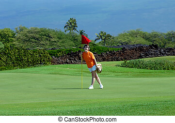 Big Island Golf Game - Woman stands besides hole marked by a...