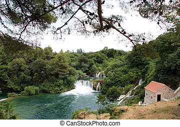 National park KRKA - Pine tree, waterfall and building in...