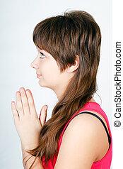 blue-eyed teen girl praying. profile
