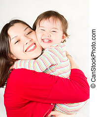 Happy mom and baby girl hugging and laughing.The concept of...