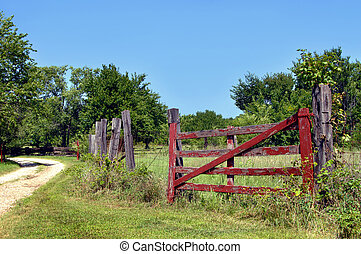 Aging Farm - Rustic red, wooden gate is overgrown with weeds...