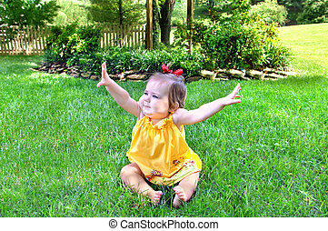Arms High - Small baby sits on the grass in park setting....