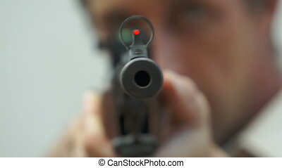 Tip of the Rifle Barrel Pointing at - Anonymous male figure...