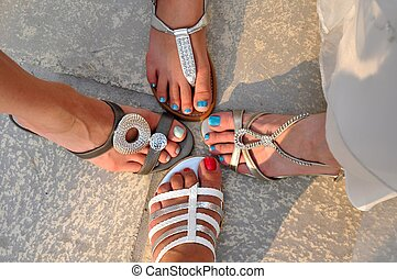 Pretty feet and shoes - Four somewhat sandy female feet with...