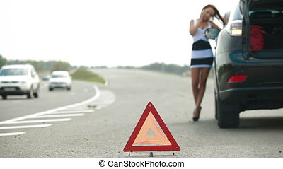 Car Troubles on the Road - Woman having car troubles on the...