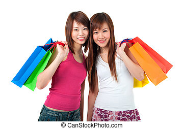 happy asian girls shopping with bags