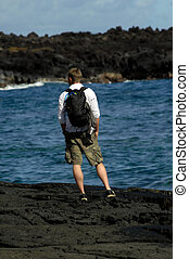 Big Island Exploring - Young man climbs over the rocky...