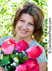 woman with a bouquet of artificial flowers in summer park